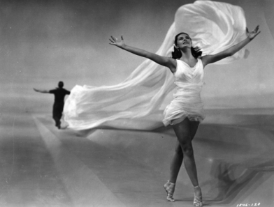 1952: Actress and dancer Cyd Charisse as the 'Elements' in a scene from the comedy musical 'Singin' In The Rain', directed by Gene Kelly and Stanley Donen for MGM. Gene Kelly (1912 - 1996) can be seen dancing in the distance. (Photo by Hulton Archive/Getty Images)