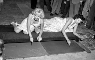 June 26, 1953. Actresses Marilyn Monroe, left, and Jane Russell write in wet cement at Grauman's Theater.