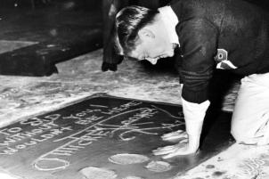 Rooney plants his hands into the cement next to his footprint and signature in the forecourt of Grauman's Chinese Theatre during induction ceremonies in Hollywood in 1938.