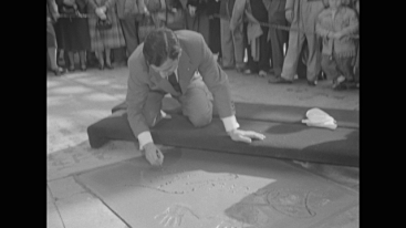 """Title card: """"Danny Thomas Joins Court of Movie Fame"""" superimposed over Thomas' hands above his signature in wet cement at Grauman's Chinese Theatre / WS pan down front of Grauman's / shot of Thomas' hand as he writes in cement / WS crowd standing, watching / MS signature / MS Thomas puts finishing touches on signature / MS Danny Thomas' wife Rose gives him a kiss on his cheek."""