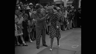 """Title card: """"Footsteps: Fame in Concrete for Ginger Rogers"""" / WS actress/dancer Ginger Rogers leans on arm of the manager of Grauman's Chinese Theatre as she steps her right foot into wet cement to leave her footprint in a collection outside the theater, part of a Hollywood tradition; spectators watch / MS manager assists Rogers as she removes her foot from the wet cement, leaving the imprint of a high-heeled shoe; Rogers looks at the imprint / CU Rogers slowly lowers her left foot, in white high-heeled shoe, into cement / spectators, primarily women, watch from behind rope line / Rogers's foot wiggles as she presses it down to make the imprint; she lifts her foot away / cutaway shot crowd watches / MS Rogers kneels on a platform stretched over the wet cement and writes an inscription in it with a stick / POV from side rear as she begins to sign her name / CU her face as she concentrates on writing in the cement / POV from side rear as she completes her signature / front shot Rogers leans forward from platform and places her hands in the cement to make handprints"""