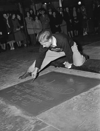 "(Original Caption) Mickey Weeps Tears of Joy. ""I've dreamt of this since I was a kid,"" says Mickey Rooney, young Metro Goldwyn Mayer star, as he puts the finishing flourish to his signature in filmdom's Hall of Fame, forecourt of the Grauman's Chinese Theater in Hollywood."