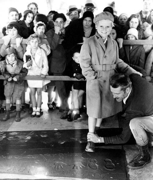 Child actor Jackie Cooper makes an imprint of his hands and feet in cement during induction ceremonies in the forecourt of Grauman's theater on Hollywood Boulevard, Ca., on Dec. 12, 1931. (AP Photo)