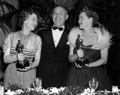 23rd February 1939: American film studio head Jack Warner (1892-1978) poses with his arms around American actors Fay Bainter (1892-1968) and Bette Davis (1908-1989), who hold their Oscars for director William Wyler's film, 'Jezebel,' at the Academy Awards, Los Angeles, California. Davis won Best Actress, and Bainter Best Supporting Actress. Davis wears an evening gown with feathers adorning her shoulders. (Photo by Hulton Archive/Getty Images)