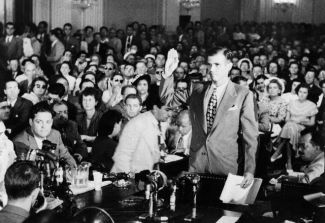 ca. August 1948, Washington, DC, USA --- Alger Hiss, accused of Communist espionage, takes an oath during hearings before the House Committee on Un-American Activities. He denied Whittaker Chambers' accusation that he was a Communist. --- Image by © Bettmann/CORBIS