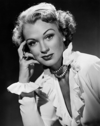 circa 1955: Headshot portrait of actor Eve Arden resting her hand on her face. She wears a double strand of pearls and a blouse with ruffled sleeves and a plunging neckline. (Photo by Hulton Archive/Getty Images)
