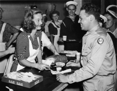 American actor Bette Davis (1908 - 1989) smiles as she serves a slice of cake to US Army private Vazquez while helping Allied troops in the Stage Door Canteen, New York City, July 10, 1943.